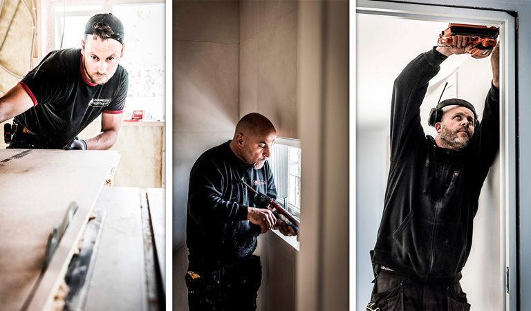 Snekker som bruker sag, fuger vindu og spikrer på plass dør